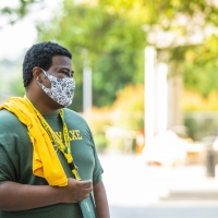 Student in spirit gear and mask on campus